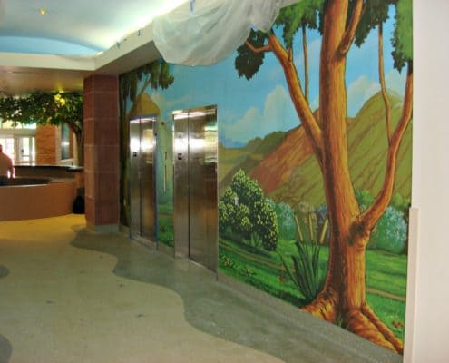 Colorful fun wall murals help soften the walls of a hospital.